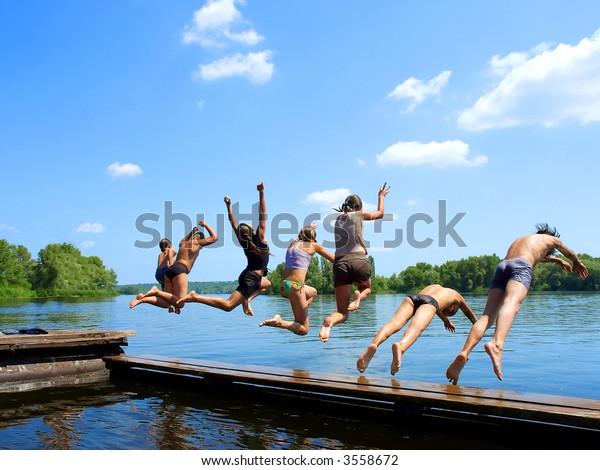 'Seven samurai' - group of kids jumps into water from pier. Shot in June, Dnieper river, Ukraine.