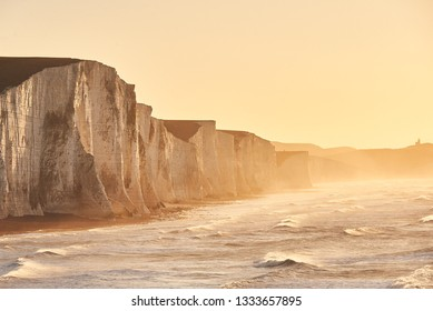 The seven Sisters and the white cliffs along the South Coast of England at sunrise, with stormy seas battering the shore.