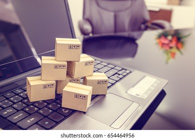 Seven small paper boxes on a laptop keyboard. Concept of online shopping that shopper or buyer can procure or buy things from seller / retailer stores on the internet, purchasing can be done at home.