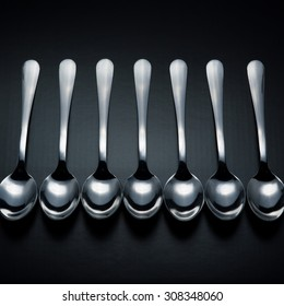 Seven stainless steel spoons on black background.