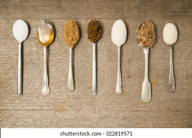 Seven teaspoons in a line with different types of sugar