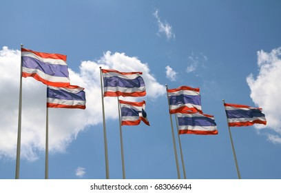 Seven Thai National flag on bright blue sky background. Blown away by wind.