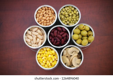 Seven tin cans with canned food on wooden background, top view