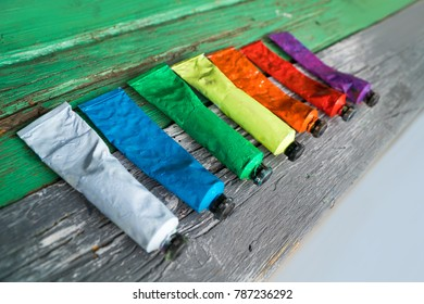 Seven tubes of multicolored paints