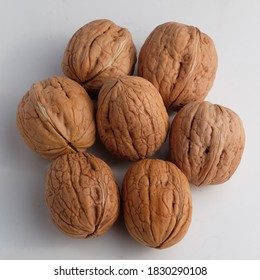 Seven unpeeled walnuts with a white background