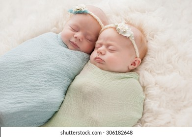 Seven week old fraternal, twin baby girls swaddled and sleeping on a white flokati rug. One sister is smiling.