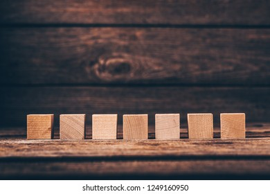 Seven Wooden Cubes on Wood Background with Copyspace
