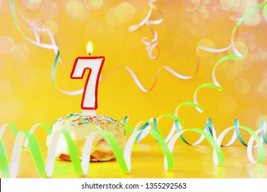 Seven years birthday. Cupcake with burning candle in the form of number 7. Bright yellow background with copy space