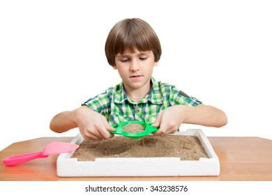 A seven years boy is sifting sand in foam plastic tray