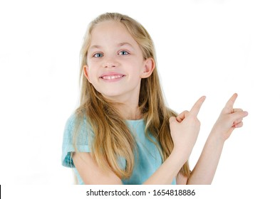 Seven years old blonde-haired little girl isolated on white background, european appearance kid feel wondered look at camera pointing fingers aside at copy space freespace for your ad text concept