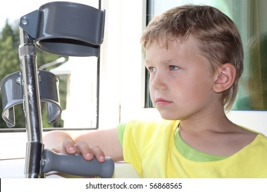 Seven years old boy with crutches sadly looks out of the window