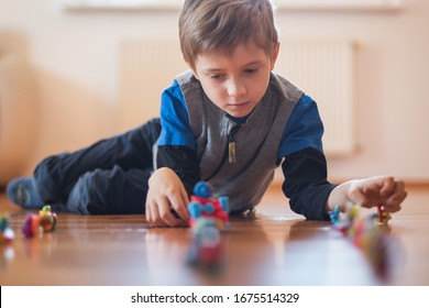 Seven years old boy playing toys on the floor
