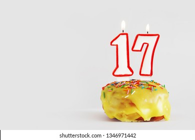 Seventeen  years anniversary. Birthday cupcake with white burning candles with red border in the form of number Seventeen. Light gray background with copy space