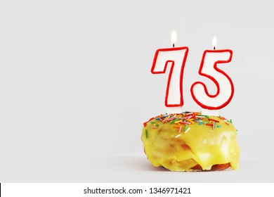 Seventy five years anniversary. Birthday cupcake with white burning candles with red border in the form of 75 number. Light gray background with copy space