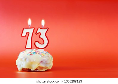 Seventy three years birthday. Cupcake with white burning candle in the form of number 73. Vivid red background with copy space
