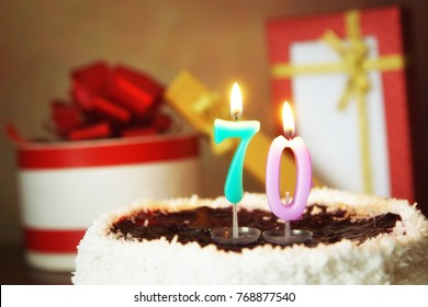 Seventy years birthday. Cake with burning candles and gifts