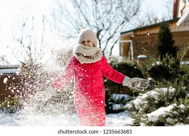 Seven-year cute girl in winter clothes playing with snow in the backyard of a house on a winter sunny day.