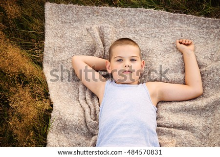dd05daf2f61 Seven-year-old boy lying down in grass in summer. Relaxing rural lifestyle