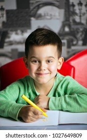 The seven-year-old boy paints the sun with a yellow felt-tip pen and smiles