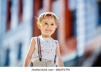 A seven-year-old boy in a sleeveless shirt and braces smiles, staring into the distance.