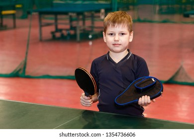 seven-year-old boy in sports form holding a case and a racket for table tennis indoors