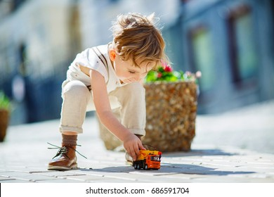 A seven-year-old boy in vintage clothes and leather shoes rolling a toy truck on a pavement