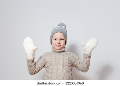 seven-year-old boy in white knitted mittens and sweater spreads his hands to the sides on a white background