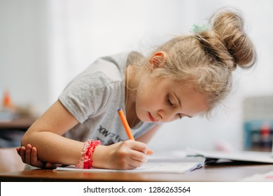 A seven-year-old girl sits at home at a table and writes in a notebook, completing a learning task or repeating lessons.