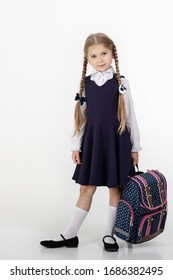 a seven-year-old schoolgirl in school uniform poses on a white background