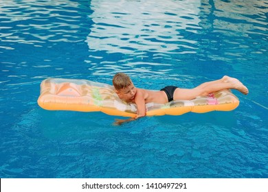seven-year-old tanned child swims on an inflatable mattress in the outdoor pool . Children and summer