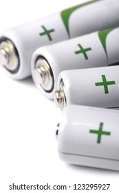 Several AA batteries closeup view on white background
