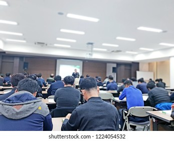 Several adult men and one male professor Lecture image