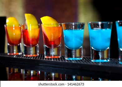 Several alcoholic shots of different drinks at a party in a nightclub on the counter