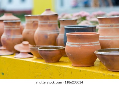 Several ancient brown clay pots of different shapes and sizes, close-up
