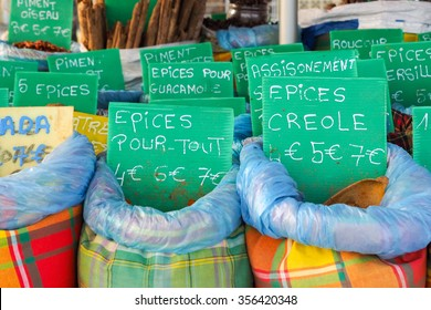 Several bags containing typical spices for cooking with tags reporting names and prices are exposed on a market stall along the road in Sainte Anne Guadeloupe.