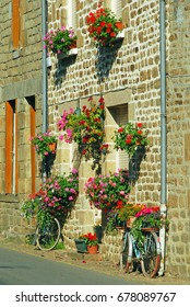 Several baskets of bright red flowers adorn the front wall of a house in a French village, Two old bicycles, also adorned with flowers, lay against the wall. July 2012