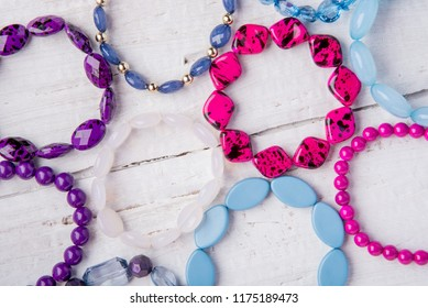 Several beautiful bracelets of beads and stones of blue, pink and purple on a white wooden background
