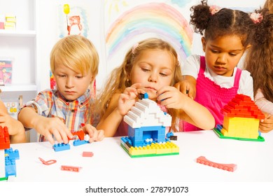 Several beautiful clever kids boys and girls playing with plastic blocks constructing houses in the kindergarten class