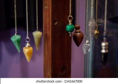 Several Beautiful Crystal Pendulums Hanging on Display