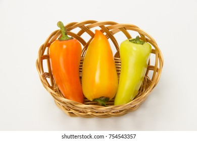 Several beautiful ripe sweet and hot peppers in a straw basket on a white background