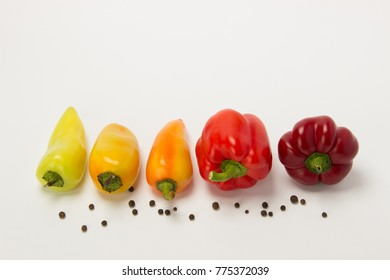 Several beautiful ripe sweet and hot peppers of red and orange on a white background