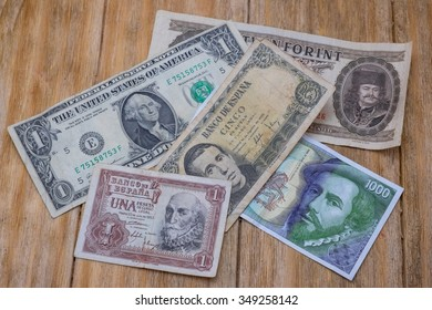 several bills Spanish pesetas, US dollar and Hungarian forint over a wooden table