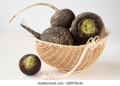 Several black radish root vegetables in a basket