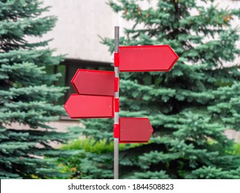 Several blank directional signs in the shape of a red arrow on a metal pole. Selection way concept