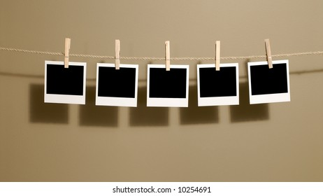 Several blank instant camera photo prints hanging on a rope or string isolated against a dark background.  Space for copy.