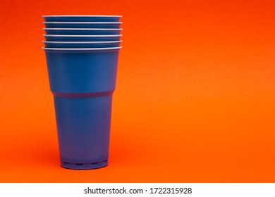 several blue plastic cups on an orange paper background - Shutterstock ID 1722315928