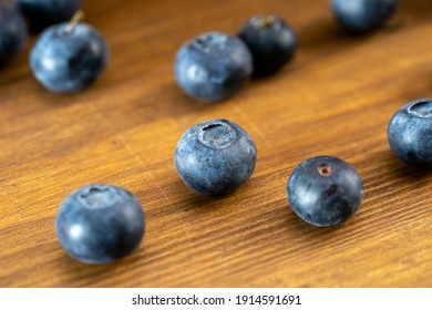 Several blueberries on a wooden table close-up.
