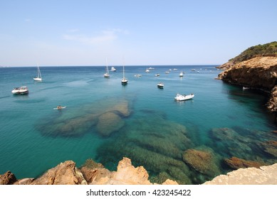 Several boats sail through crystal waters close to beautiful village and beach of Sa Riera, Mediterranean sea, Catalonia, Spain