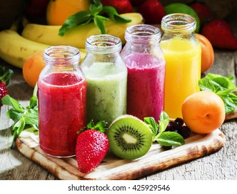 Several bottles with fruit and berry juices, vintage wooden background, selective focus
