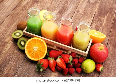 several bottles with fruit and berry juices smoothies and milkshakes , vintage wooden background